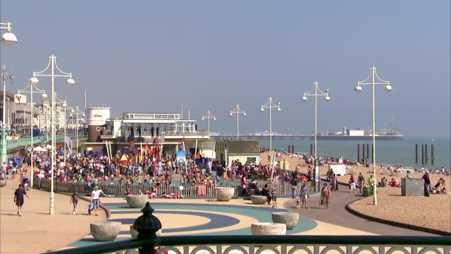vacationers enjoy brighton beach and brighton pier. available in hd. - ブライトン パレスピア点の映像素材/bロール