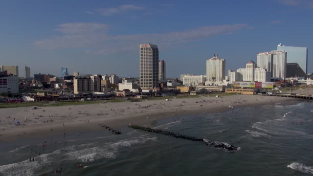 vacationers use the beach near the boardwalk and casinos at atlantic city. - new jersey stock videos & royalty-free footage