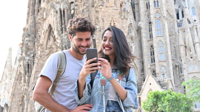 vacationing couple taking selfie at sagrada familia - church stock videos & royalty-free footage
