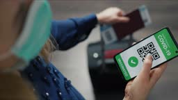 vaccinated tourist using digital health passport app in mobile phone in airport for safe travel during covid-19 pandemic