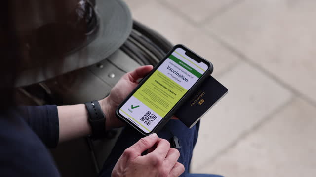 vaccinated woman using digital vaccine passport app in mobile phone for travel during covid-19 pandemic - gate stock videos & royalty-free footage