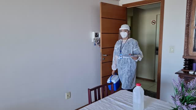 vaccination at home. female nurse getting in a house living room carrying a cooler - pardo brazilian stock videos & royalty-free footage