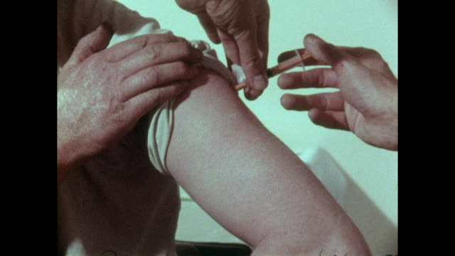 "vídeos y material grabado en eventos de stock de vaccination in arm and doctor saying ""next please""; 1973 - inyectar"