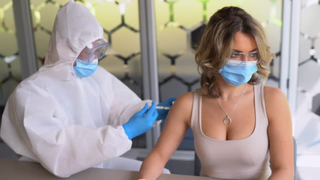 vaccination - the doctor in a protective suit gives the vaccine to the patient - flu vaccine stock videos & royalty-free footage