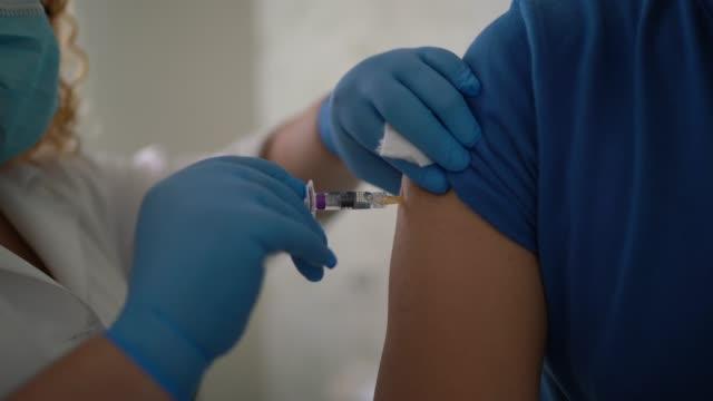 stockvideo's en b-roll-footage met vaccin dat in de arm van een patiënt wordt toegepast - griepvaccin