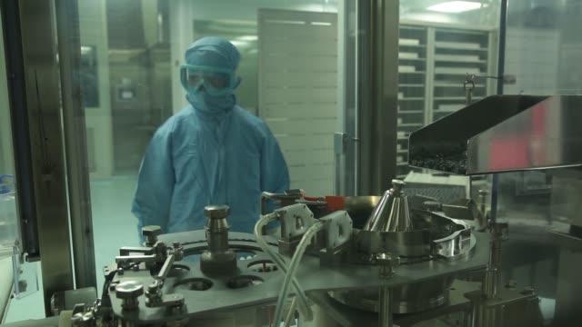 vídeos de stock, filmes e b-roll de ms vaccine vials pass through a filling and capping machine ms a technician monitors vaccine vials passing through a filling and capping machine - artigos de vidro de laboratório