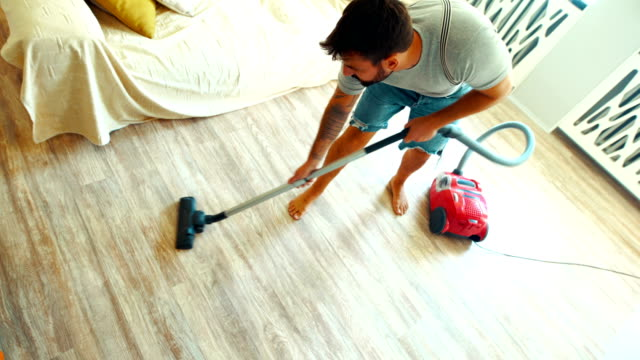 vacuuming the living room floor. - lavori di casa video stock e b–roll