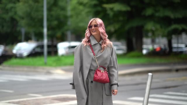 valentina ferragni wears sunglasses, a gray coat, gray dress with shirt collar, red pointy heeled shoes, a red studded bag, outside the fendi show... - milan fashion week stock videos & royalty-free footage