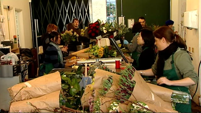 valentine's day environmental cost of red roses england london int florists preparing bunches of flowers in busy florest's shop man delivering... - valentinstag stock-videos und b-roll-filmmaterial
