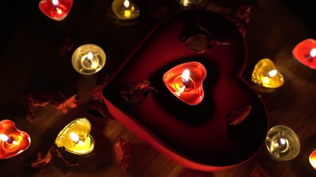 4k valentinstag romantik mit rotem herzen, kerzen und rosenblättern. - candlelight stock-videos und b-roll-filmmaterial