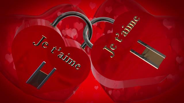 バレンタインの日に 2 つの心と形フランス語フレーズ ジュテームと赤い南京錠、2 つの赤い 3 d ハートを打つ、バック グラウンドでハート形の粒子が動いて、あなたを愛して - johnfscott点の映像素材/bロール