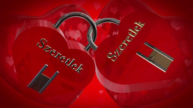 2 ハートと一緒にバレンタインデーの形 szeretlek のハンガリー語のフレーズと赤い南京錠、2 つの赤い 3 d ハートを打つ、バック グラウンドでハート形の粒子が動いて、あなたを愛して - johnfscott点の映像素材/bロール