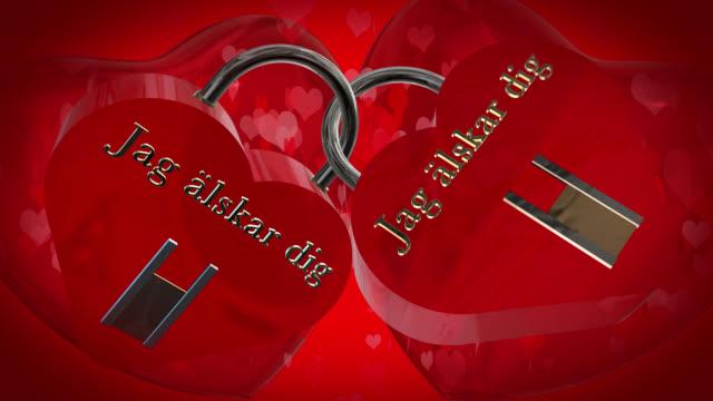バレンタインの日に 2 つの心と形スウェーデン フレーズ ジャグ älskar 掘るで赤い南京錠、2 つの赤い 3 d ハートを打つ、バック グラウンドでハート形の粒子が動いて、あなたを愛して - johnfscott点の映像素材/bロール