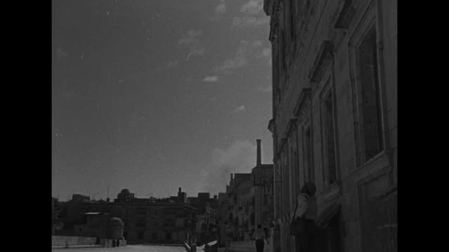 valletta civilians moving quickly through streets during air raid / man running looking back at camera / ms civilians and soldiers walking into bomb... - axis powers stock videos & royalty-free footage