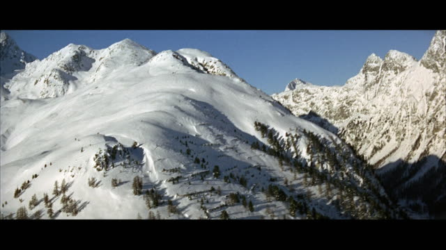 vídeos de stock, filmes e b-roll de 1967 low aerial valley and alpine peaks covered with snow - formato letterbox