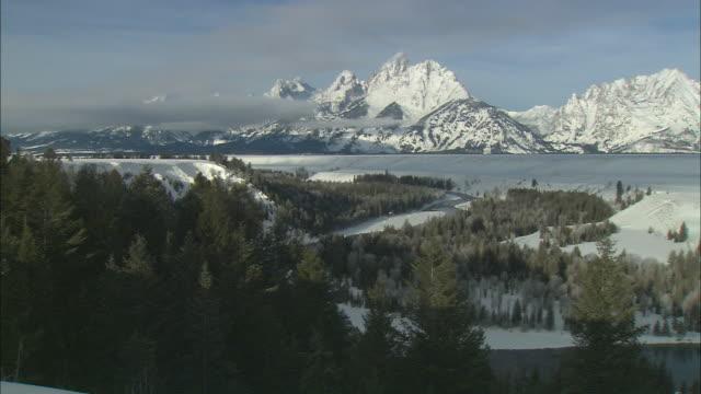 ws zi valley and rugged, jagged snow covered mountains / grand teton national park, wyoming, usa - ロッキー山脈点の映像素材/bロール
