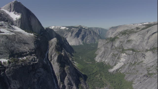 a valley lies far below the towering mountain peaks of yosemite national park. available in hd. - yosemite nationalpark stock-videos und b-roll-filmmaterial