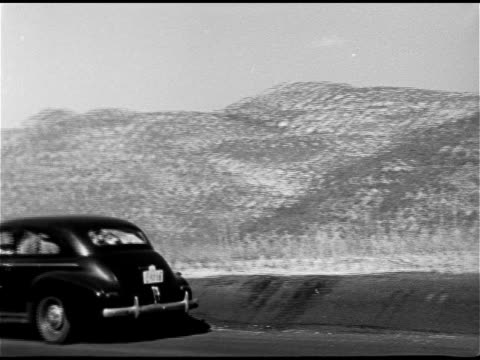 stockvideo's en b-roll-footage met valley mountains sedan pulling off road family in car mother father two boys in matching striped shirts looking out windows ws valley w/ mountains bg... - 1948
