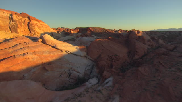 WS AERIAL Valley of Fire in morning with sunshine and rock formations with different red colors / Nevada, United States