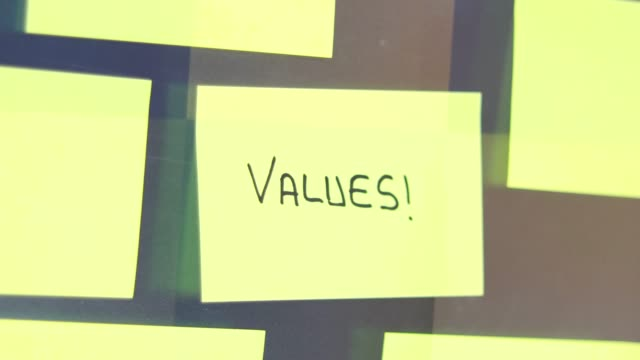 values post-it concept. businessman sticks a post-it on the glass of meeting room. - adhesive note stock videos & royalty-free footage