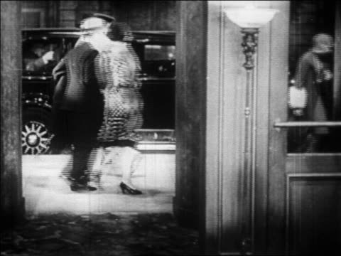 "vidéos et rushes de b/w 1928 ""vamp"" woman slowly walking by doorway / people getting out of cars in background / nyc / newsreel - 1928"