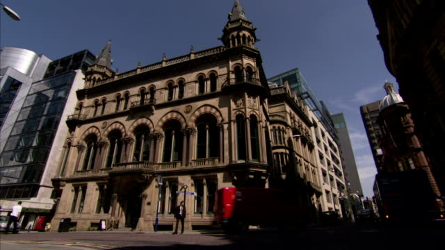 a van and a few pedestrians pass the manchester town hall in england. available in hd. - rathaus stock-videos und b-roll-filmmaterial