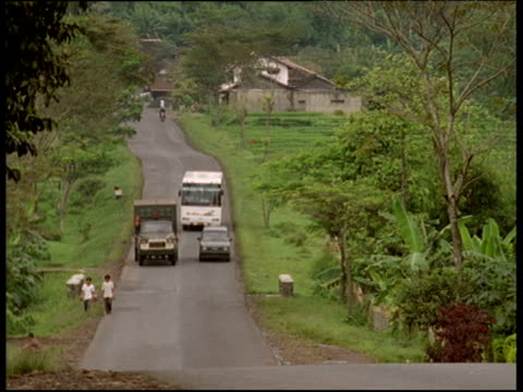 van and coach over take car on narrow road java - overtaking stock videos and b-roll footage