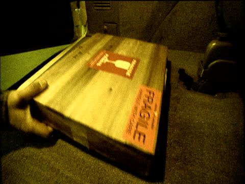 vídeos de stock, filmes e b-roll de van door opens and a box marked fragile is placed inside boot of vehicle, door is slammed shut - fragilidade