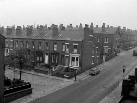 A van drives past a row of terraced houses in Leeds