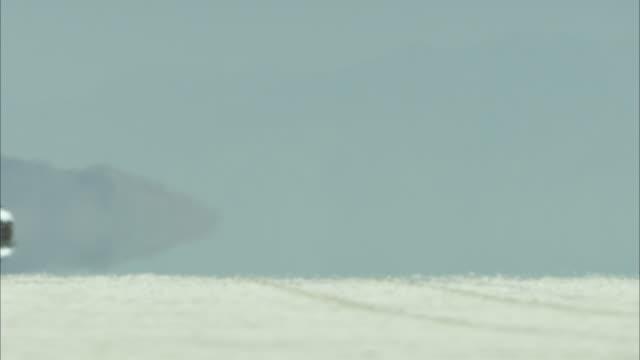 van driving across white sand desert - 熱波点の映像素材/bロール