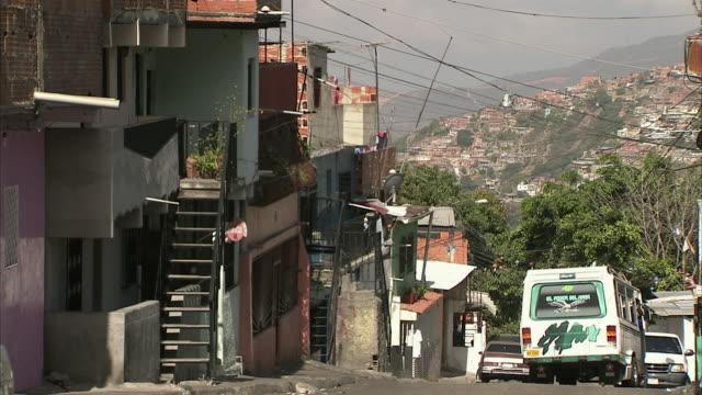 WS Van driving away from poor block of houses in Federico Quiroz / Metropolitan District of Caracas, Miranda, Venezuela