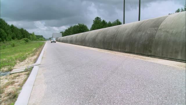 vídeos de stock, filmes e b-roll de ts van driving on a narrow road next to a covered concrete tunnel - tunnel