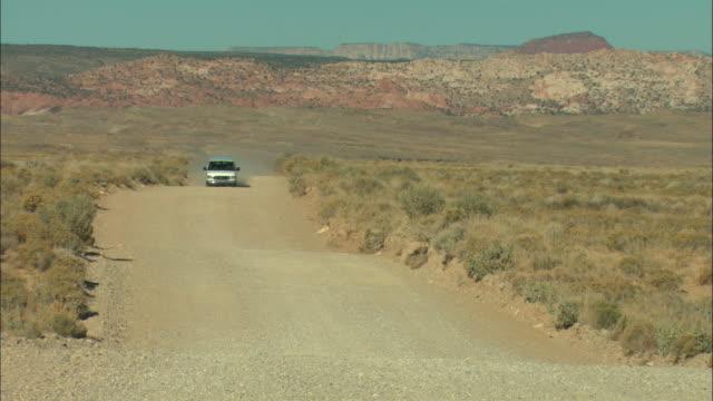 ws, van driving on gravel road through plateau landscape, utah, usa - ländliche straße stock-videos und b-roll-filmmaterial