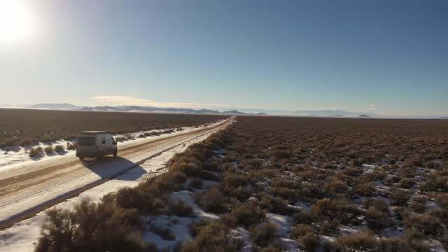 ニューメキシコ山脈近くの遠隔地道路を走行するバン - winter点の映像素材/bロール
