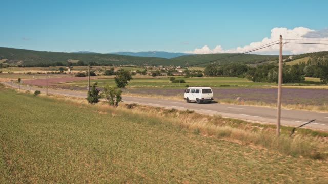 van moving on country road amidst field - country road stock videos & royalty-free footage