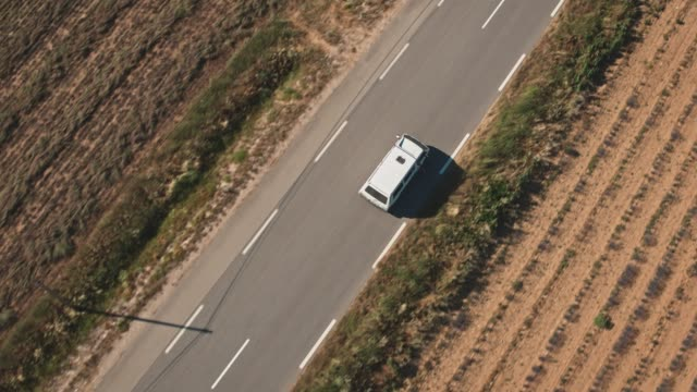 van moving on country road amidst field - van vehicle stock videos and b-roll footage