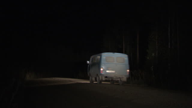 a van travels along a forest road at night. - van stock videos & royalty-free footage