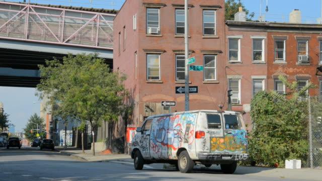 ts van with graffiti parked near rundown buildings under williamsburg bridge ramp / brooklyn, new york, usa - heruntergekommen stock-videos und b-roll-filmmaterial