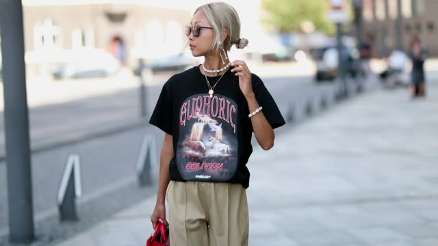 Vanessa Hong wearing band tshirt beige pants red bag is seen outside Designers Remix during the Copenhagen Fashion Week Spring/Summer 2019 on August...