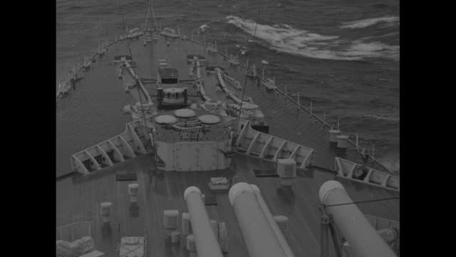 hms vanguard at sea in heavy gale / waves splash over the deck / pov looking thru rigging to royal standard flapping / king george vi plays deck... - princess elizabeth stock videos and b-roll footage