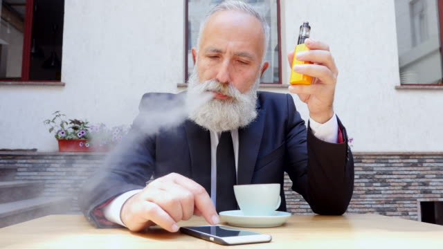 vaping - brief. bearded businessman smokes an e-cigarette in a summer restaurant - cigarette stock videos & royalty-free footage