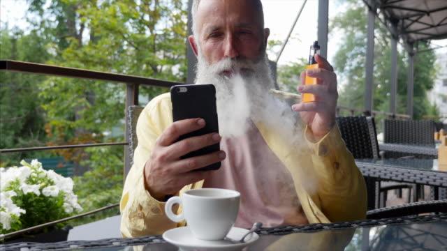 vídeos y material grabado en eventos de stock de vaping - breve. canas feliz barbudo fumando un cigarrillo electrónico en un café - t mobile