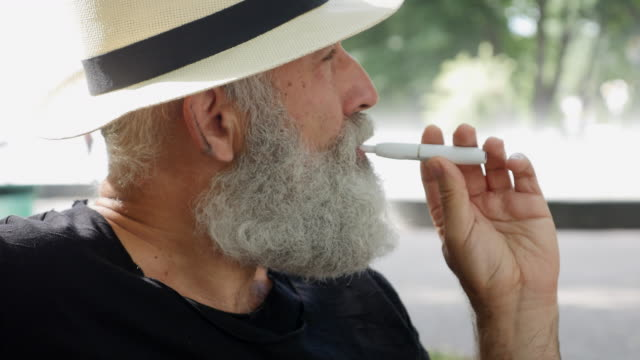 vaping - brief. bearded happy man smoking an electronic cigarette in the park - black shirt stock videos & royalty-free footage