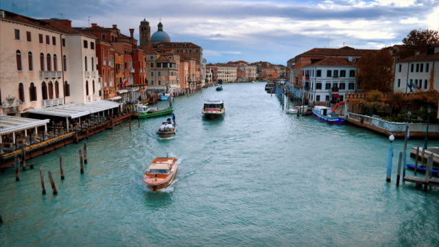 vaporetto and commercial boats traverse the grand canal in venice, italy - barca a motore video stock e b–roll