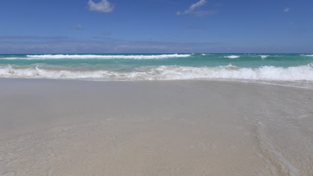 varadero beach time lapse of blue water waves in the white sand. the sea gets close to the camera. beauty of cuban nature-varadero,cuba - varadero stock videos and b-roll footage