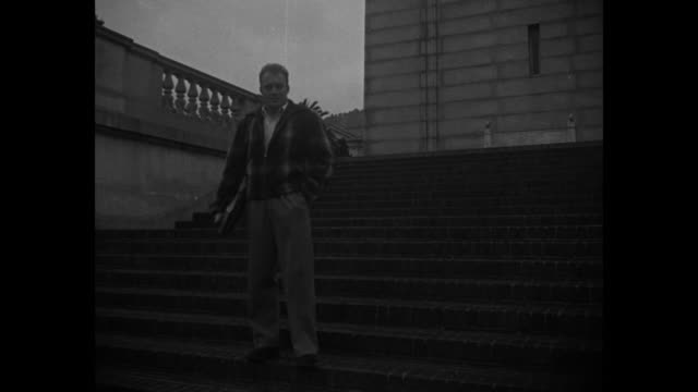 vard stockton in civilian clothes walking down steps towards camera at the university of california he stops and poses for photo opportunity then... - university of california bildbanksvideor och videomaterial från bakom kulisserna