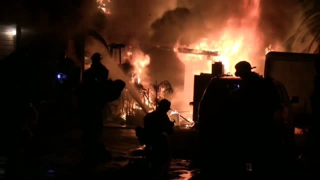 varied shots of firefighters battling a major 4-alarm house fire in national city, california. multiple explosions are visible/audible at 2:00 - 2:20. - fire protection suit stock videos & royalty-free footage