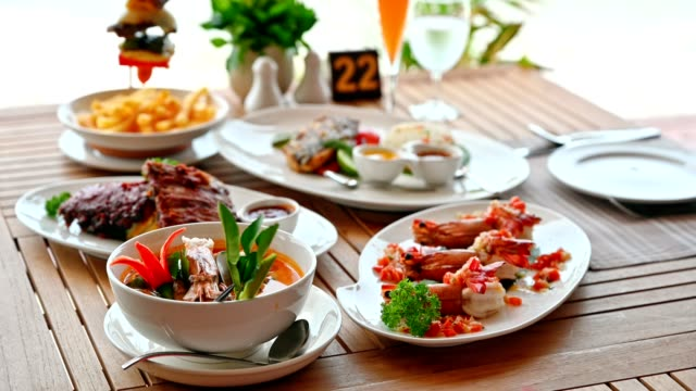 variety food with shrimp spicy, fried pork ribs, tom yum goong, beef steak on wooden dining table on restaurant patio - tradition stock videos & royalty-free footage