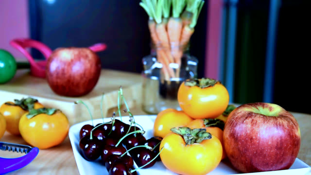 Variety fruits on table in colorful kitchen/ healthy lifestyle conceptual
