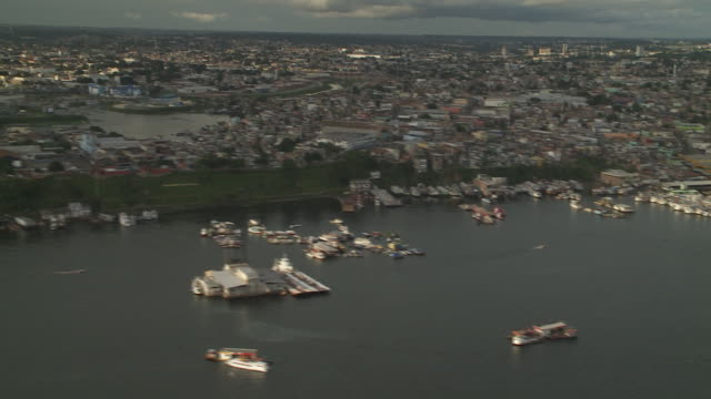 a variety of boats and ships crowd the docks along a river in manaus, brazil. - manaus stock videos and b-roll footage